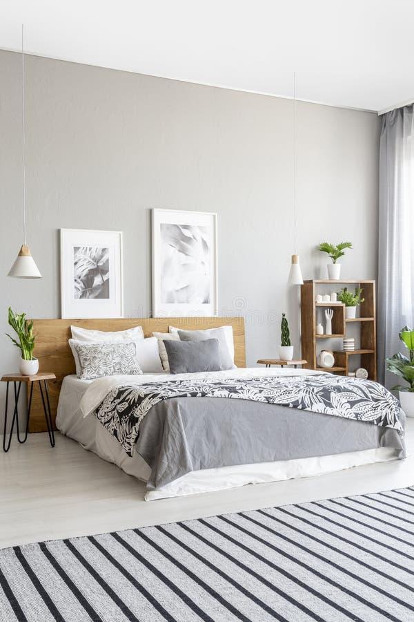 Tapis rayé dans l'intérieur gris de chambre à coucher avec des affiches au-dessus du lit W image libre de droits