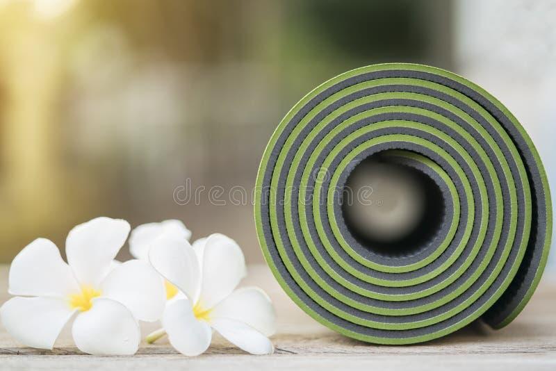 Tapis vert de yoga et fleurs image stock