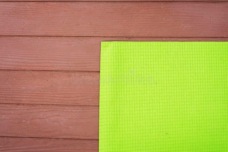 tapis vert de yoga pour le yoga de pratique sur le plancher en bois image stock