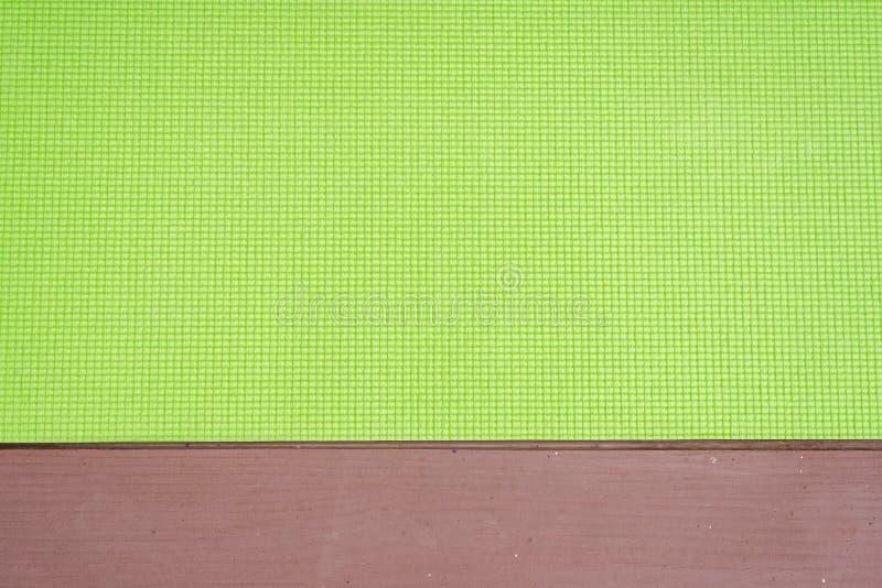 tapis vert de yoga pour le yoga de pratique sur le plancher en bois photo stock
