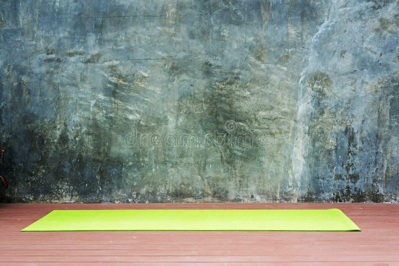 tapis vert de yoga pour le yoga de pratique sur le plancher en bois avec urbain/wa images stock