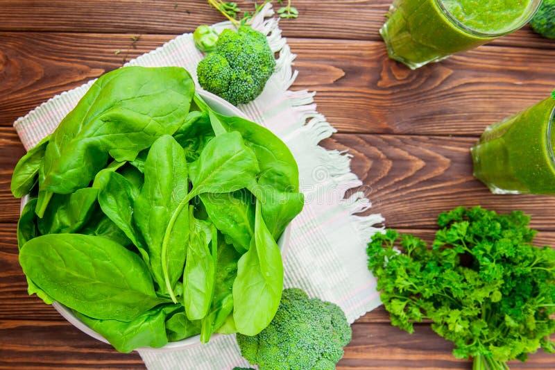 Tappar nya spenatsidor för bästa sikt med vatten i keramisk bunke, och annan den gräsplanörter, broccoli och smoothien på det mör royaltyfri bild