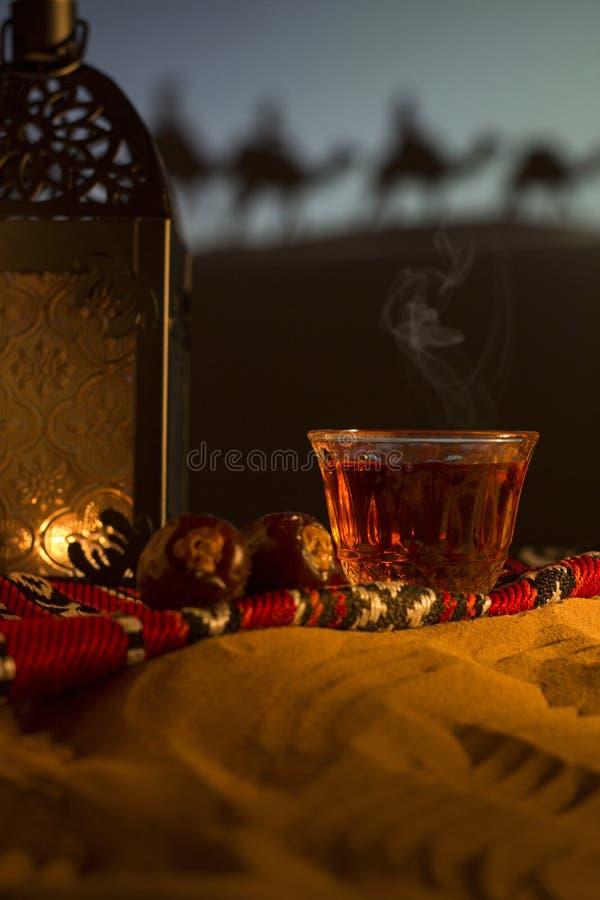 Tappeto arabo con le tazze di tè, lanterna, date, cammelli in dune di sabbia del deserto immagine stock