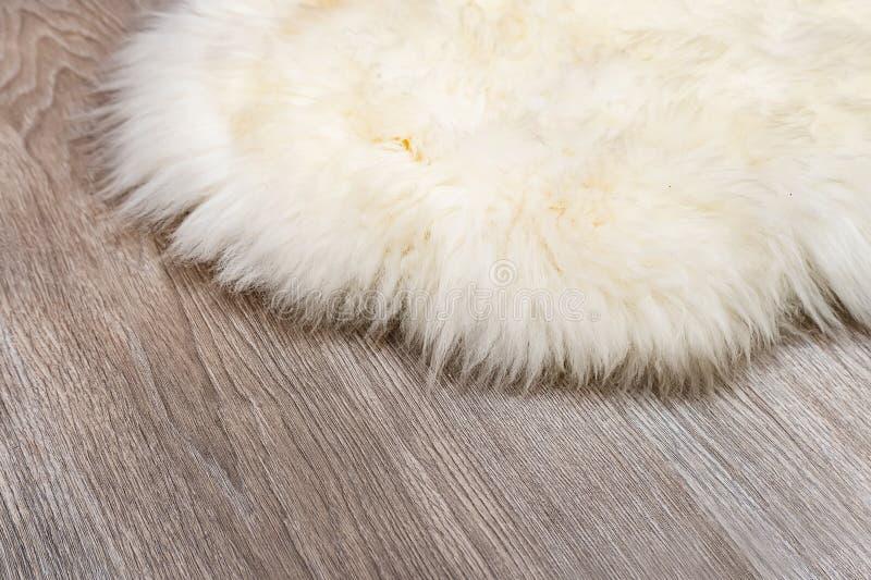 Tappeto decorativo della pelliccia sul fondo di legno del pavimento fotografia stock libera da diritti