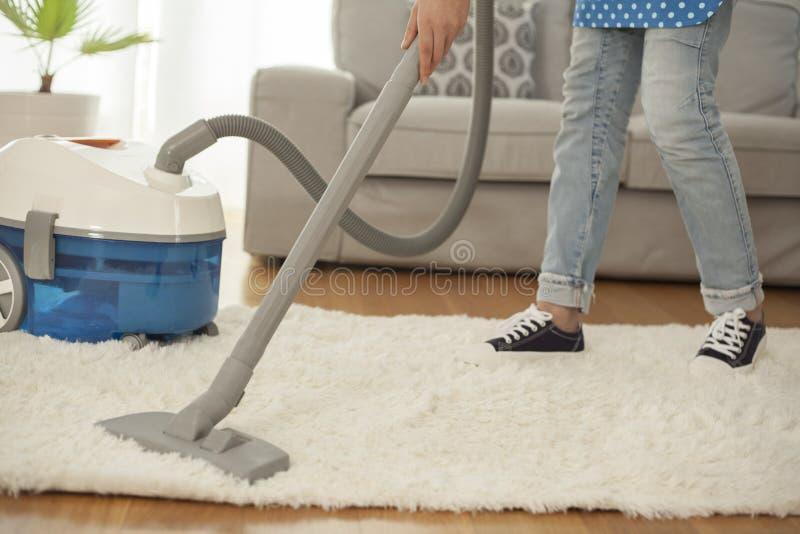 Tappeto di pulizia della donna con un aspirapolvere nella sala immagini stock libere da diritti