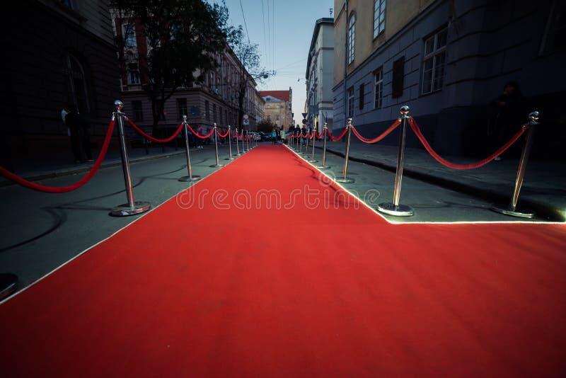 Tappeto rosso lungo fra le barriere della corda sull'entrata immagine stock