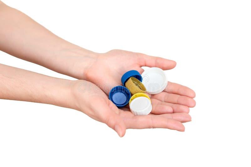 Tappi di bottiglia femminili della plastica della tenuta della mano Due mani con i coperchi di plastica Spreco riciclabile Ricicl fotografia stock