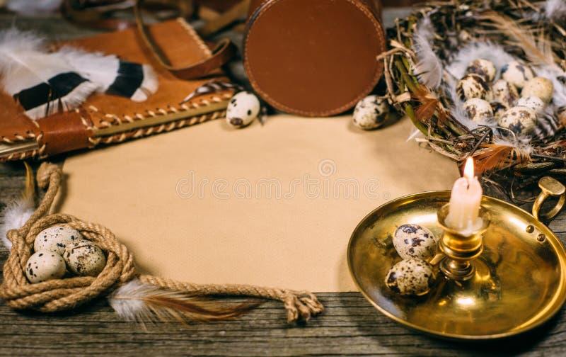 Tappningåtlöje upp på gammalt wood bräde Ljusstake, ägg inom liten korg, anteckningsbok, stycke av repet och ark av papper royaltyfri bild