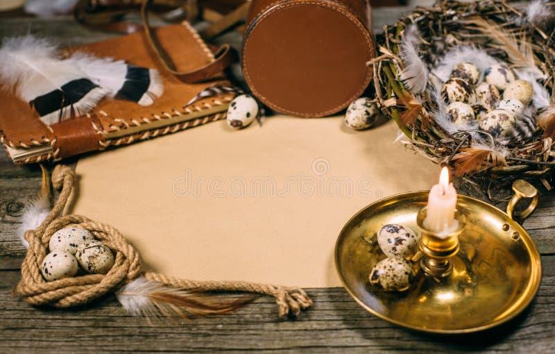 Tappningåtlöje upp på lantligt wood bräde Ljusstake, ägginsidarede, anteckningsbok, spole av repet och ark av papper arkivfoto