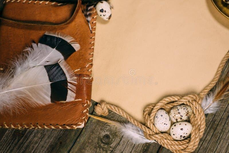 Tappningåtlöje upp på lantligt wood bräde Ljusstake, inre spole för ägg av repet, anteckningsbok och ark av papper arkivfoton