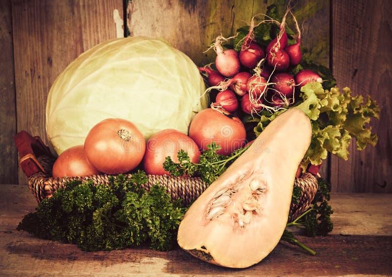 Frukter och grönsaker på en korg med en lantlig bakgrund fotografering för bildbyråer