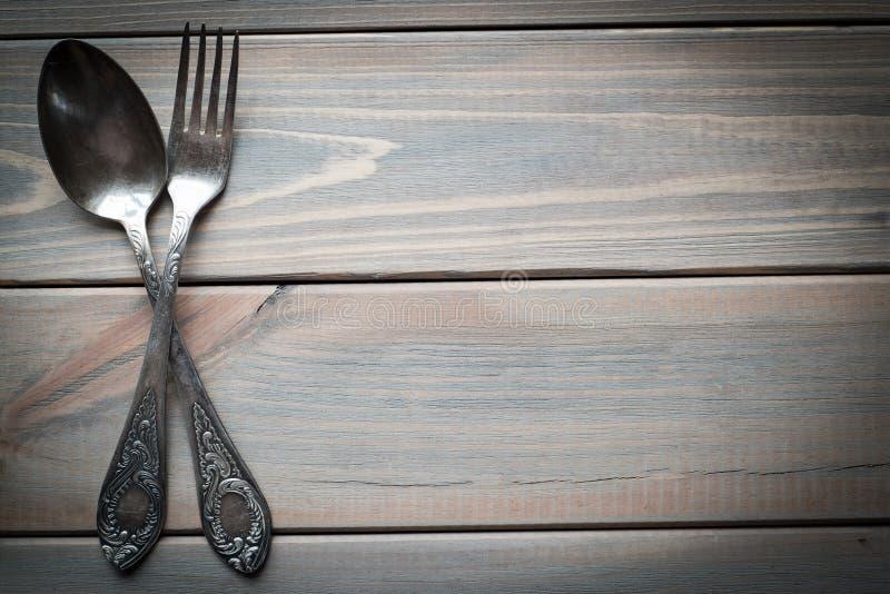 Tappning försilvrar skeden och gaffeln på en träbakgrund utensils för service för anddatalistkök trevliga royaltyfria bilder