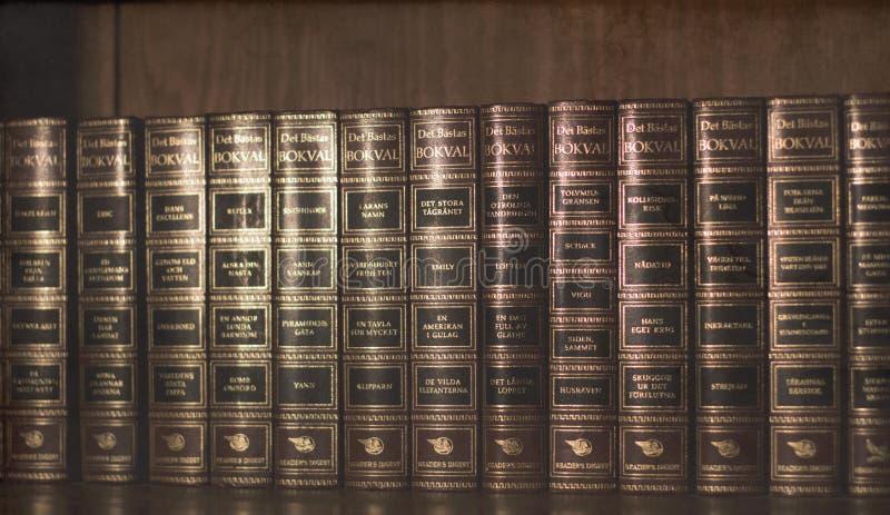 Tappning gamla böcker i träbokhylla royaltyfria foton