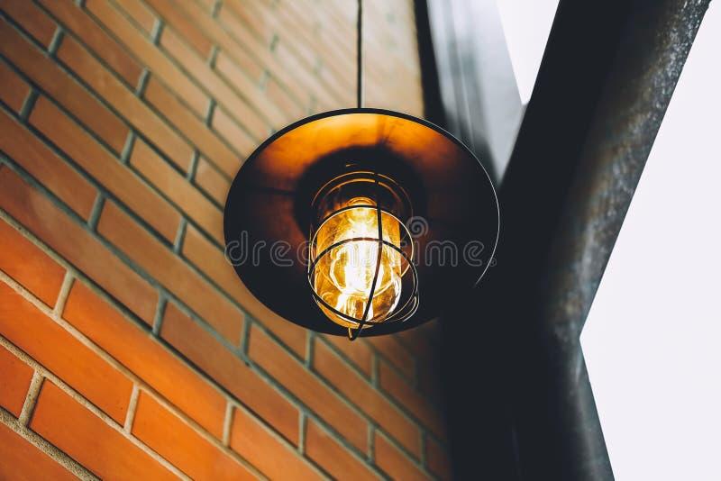 Tappning LEDDE den edison lampan eller den glödande ljusa kulan i restaurang eller kafét med den forntida kvarterväggen med brun  fotografering för bildbyråer