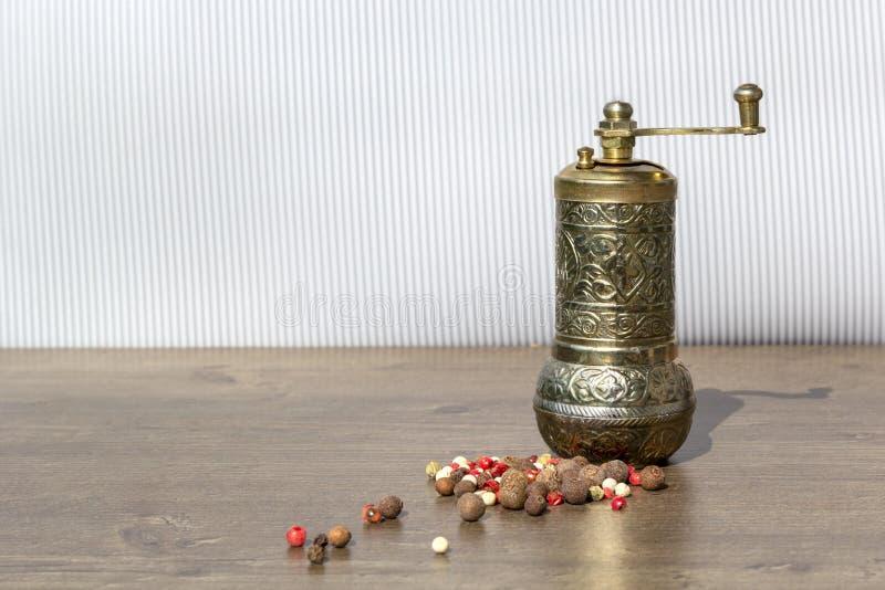 Tappning maler för peppar med svarta pepparkorn och kryddpeppar på trätabellen Kökanordningar för att mala kryddor och att salta royaltyfri foto
