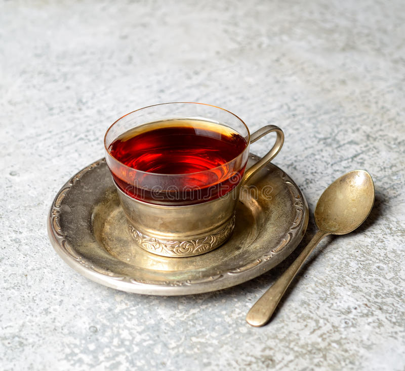 Tappning rånar med doftande te på ett metalltefat och tesked på en bakgrund för grå färger t arkivbild