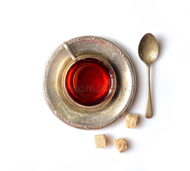 Tappning rånar med doftande te på ett metalltefat, socker, en tesked på en vit bakgrund royaltyfri bild