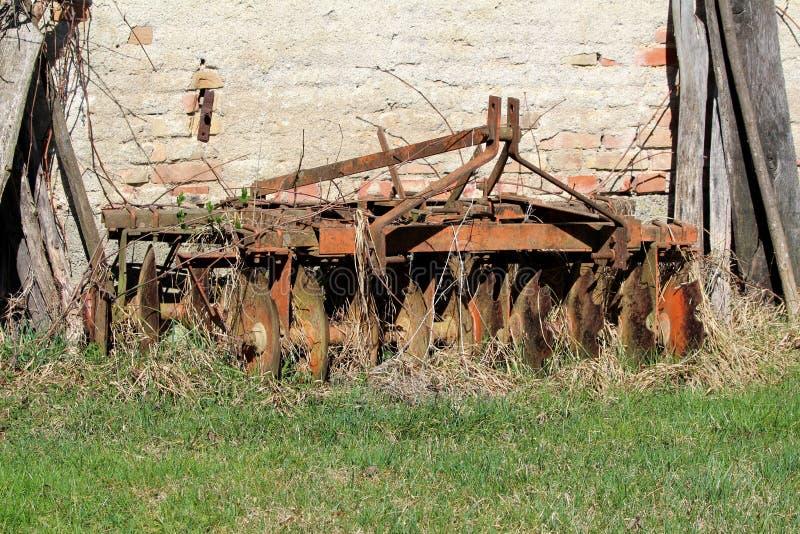 Tappning rostade gamla harv som lämnades i trädgården som delvist var bevuxen med torkat gräs som omgavs med oklippt gräs och trä royaltyfri bild