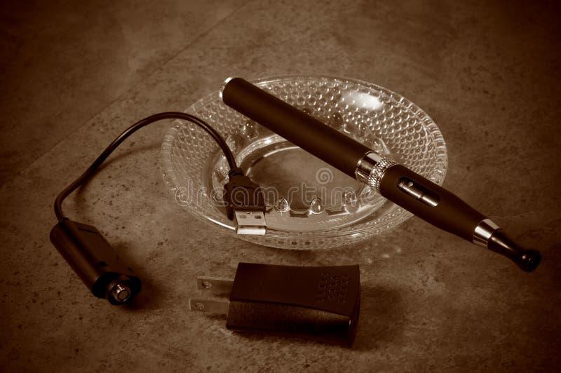 Tappning som ser den elektroniska cigaretten med uppladdaren royaltyfri bild