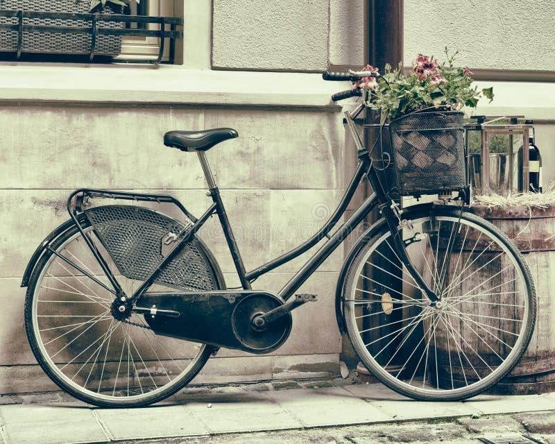 Tappning stiliserade fotoet av bärande blommor för den gamla cykeln royaltyfri bild
