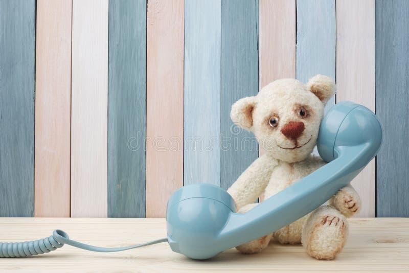 Tappning Teddy Bear med den retro telefonen på träbakgrund arkivfoton