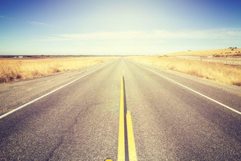 Tappning tonad ändlös landsväg arkivfoton