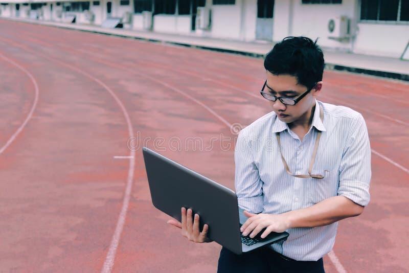 Tappning tonade bild av den yrkesmässiga unga asiatiska affärsmannen med bärbar datoranseende på loppspår vision för exponeringsg royaltyfria bilder