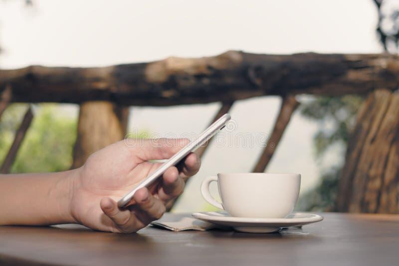 Tappning tonade bild av kaffekoppen med händer av den hållande mobiltelefonen för den unga mannen i naturbakgrund Selektiv fokus  arkivfoto