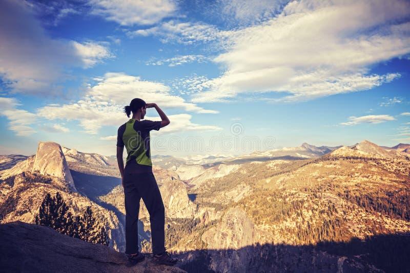 Tappning tonade konturn av en hållande ögonen på bergsikt för kvinna royaltyfria bilder