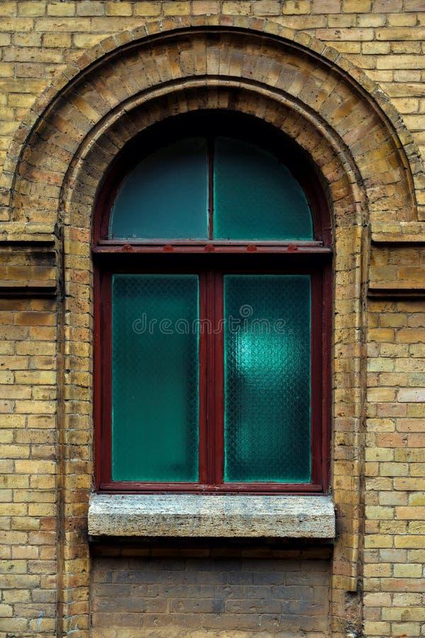 Tappning välva sig fönstret i väggen av gul tegelsten Gräsplan - färgerna av havsvågexponeringsglas i ett rödbrunt mörker - rött  royaltyfri bild