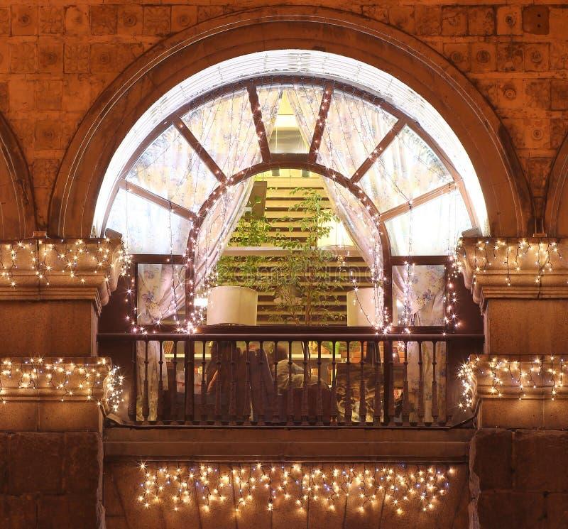 Tappning välva sig fönstret med balkongen på natten som dekorerades med många julljus arkivfoton