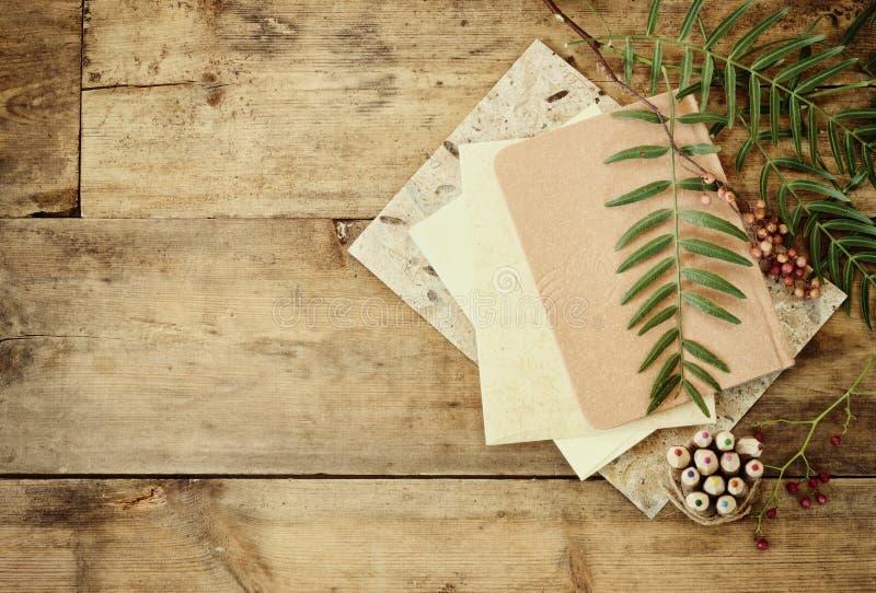 Tappninganteckningsbok, gammalt papper och bunt av färgrika träblyertspennor över trätabellen ordna till för modell arkivbild