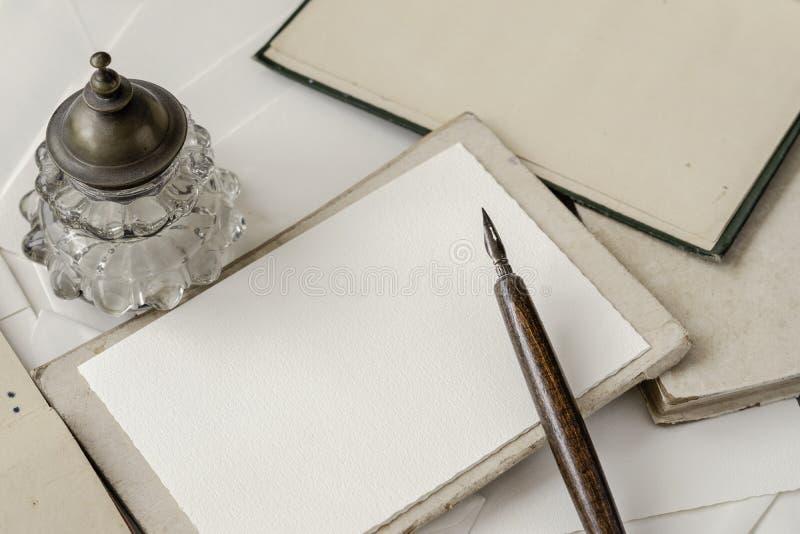 Tappningbakgrund med stället för text med caligraphic handskrift, den gamla träpennan och bläckhornen, lägenhet lägger royaltyfri bild