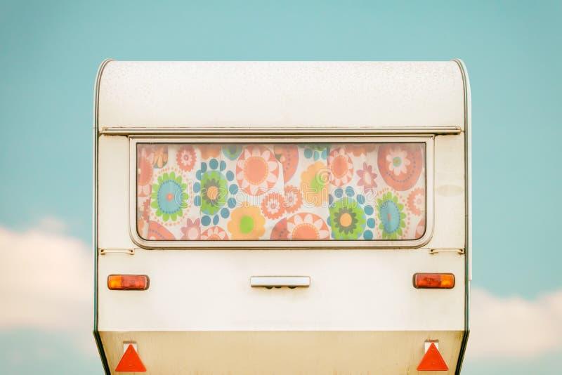 Tappningbaksidan av en husvagn med seventies blommar gardiner royaltyfri foto