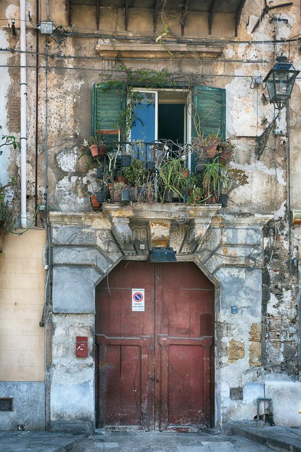 Tappningbalkong med olika blommor, sprucken murbruk och trädörrar, medelhavs- stil arkivbild