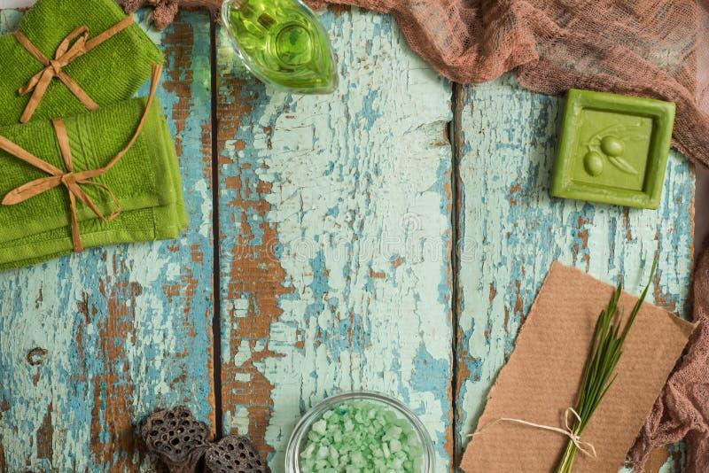 Tappningbegrepp av den gröna brunnsorten Olivgrön handgjord tvål, gröna handdukar, salt hav och en trähårkam för håromsorg På en  royaltyfria bilder