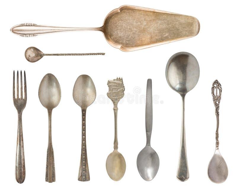 Tappningbestick, antika skedar, knivar, kakaskyfflar som isoleras på isolerad vit bakgrund antik silverware retro arkivfoto
