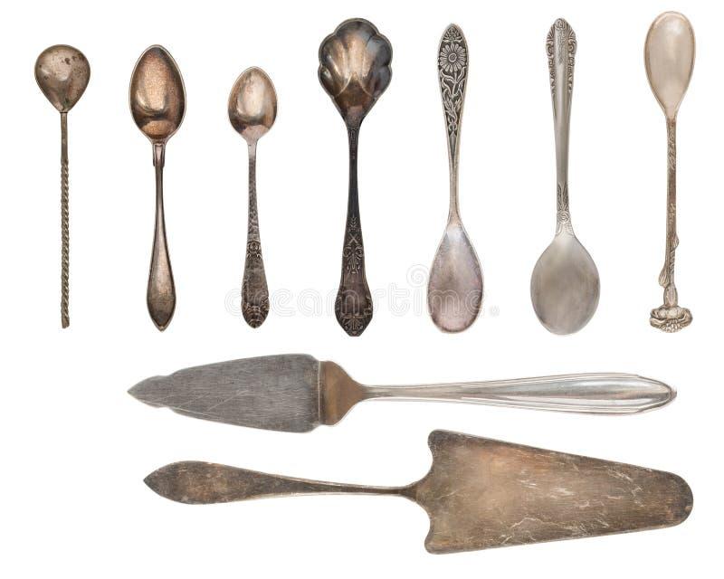 Tappningbestick, antika skedar, knivar, kakaskyfflar som isoleras på isolerad vit bakgrund antik silverware retro royaltyfri fotografi