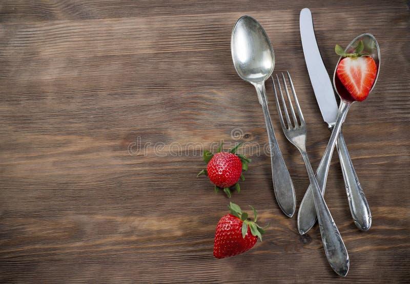 Tappningbestick på den bruna tabellen med jordgubben royaltyfria foton
