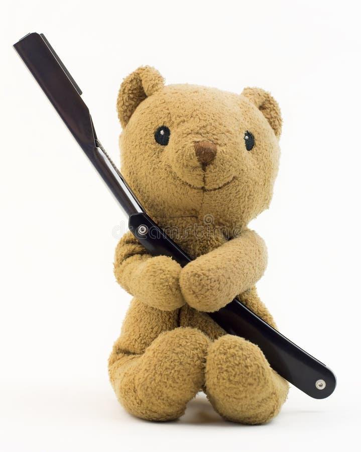 Tappningbjörnleksak (den gamla björnen leker med den svarta raka rakkniven), arkivbild