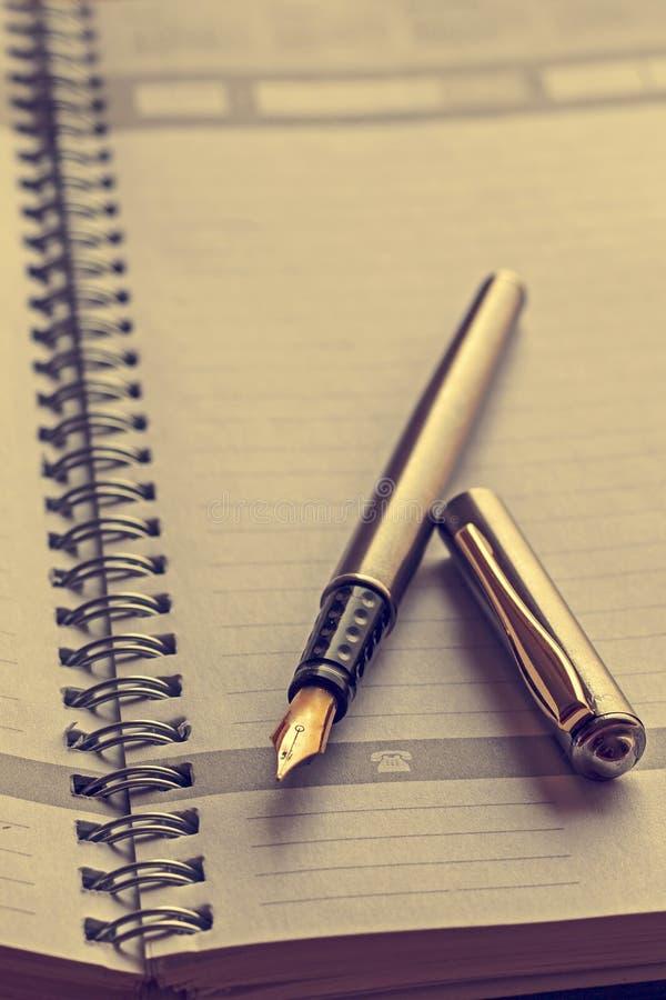 Tappningblick på en öppen anteckningsbok med en reservoarpenna arkivbilder