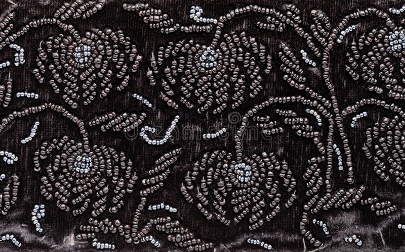 Tappningbroderi vid svarta pärlor på svart sammet fotografering för bildbyråer