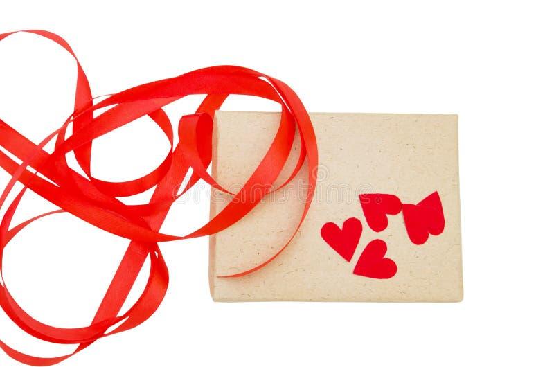Tappningbrunt slogg in gåvaasken med det röda bandet och hjärta som isolerades på vit bakgrund, den bästa sikten, snabb bana arkivbilder