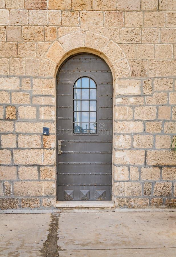Tappningdörr med metallbälten och nitar och gallerförsett fönster, Stella Maris Monastery i Haifa fotografering för bildbyråer