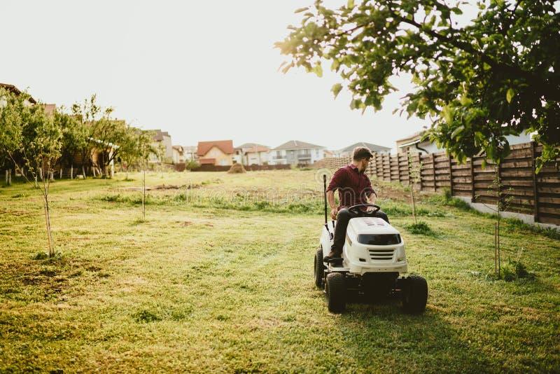 Tappningeffekt av att landskap arbeten Manlig arbetare som rider en traktorgräsbeskärare royaltyfria bilder