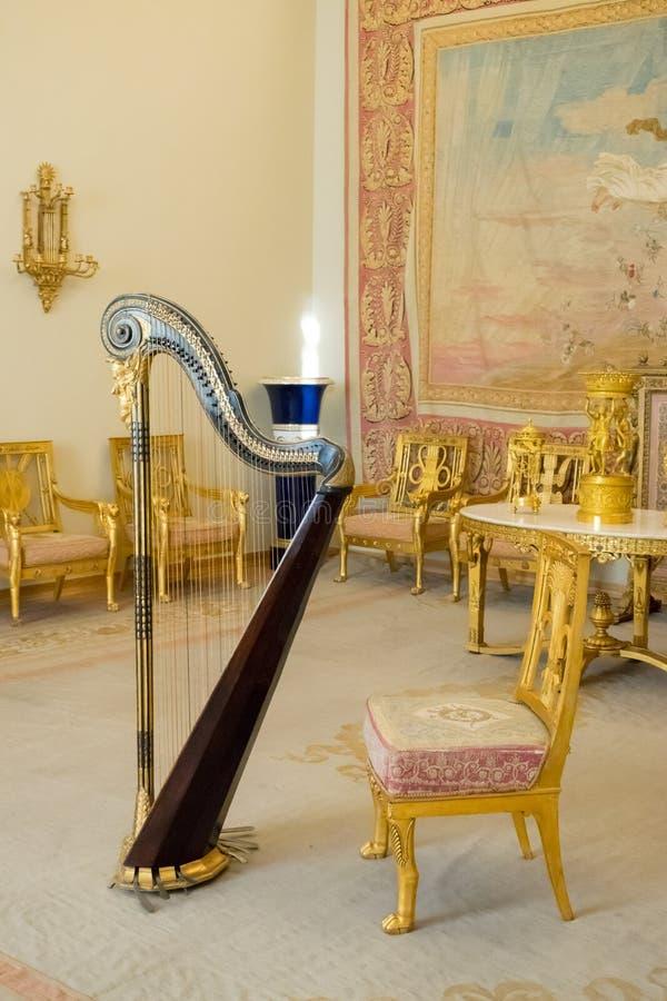 Tappningfåtölj i rum med guld- garnering royaltyfri bild