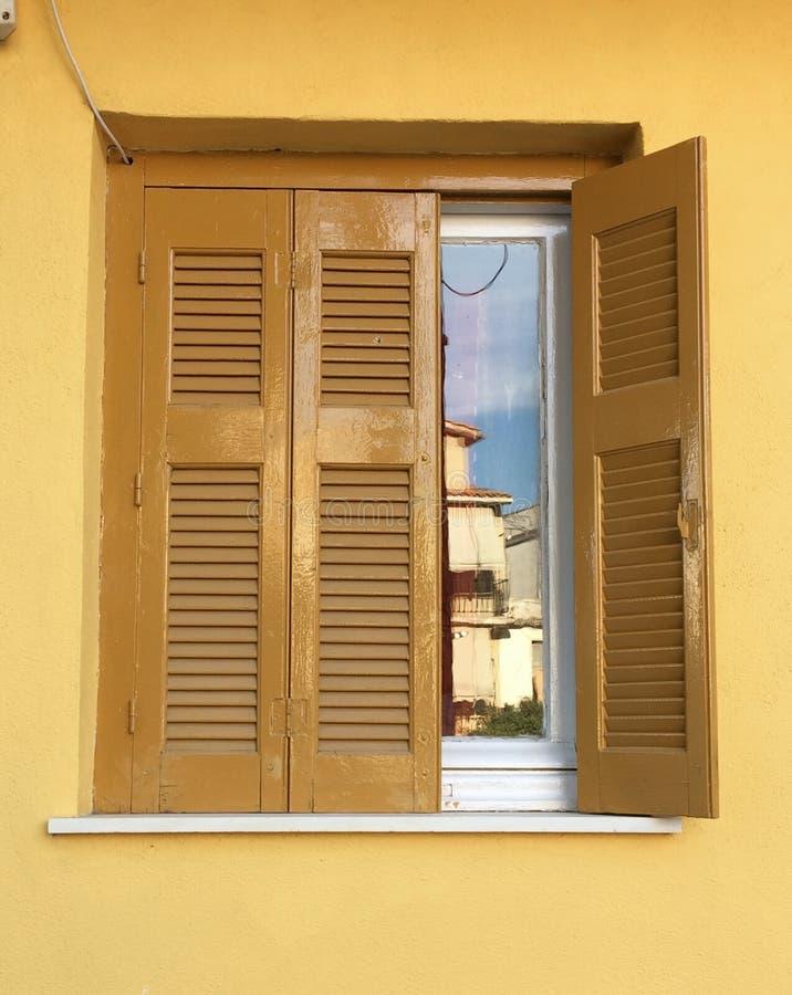 Tappningfönster med antika gula slutare på gul kulör fasade royaltyfria foton