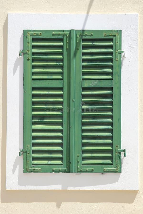 Tappningfönster med slutare över den vita väggen arkivbild