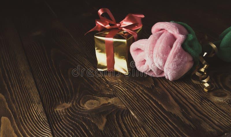 Tappningferie-/romantiker-/valentindagbakgrund med rosa plysch och gåvaasken på trätabellen arkivfoton