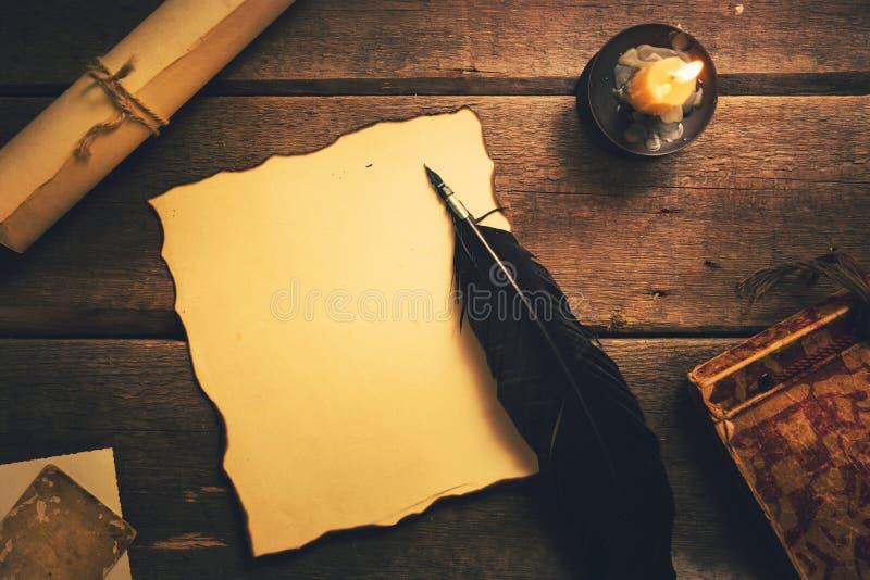 Tappningfjäderpenna på det gamla arket för tomt papper royaltyfria bilder
